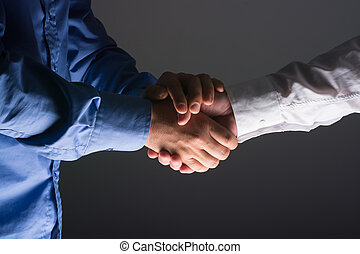 Handshake Handshaking in dark with - Two Businessman...