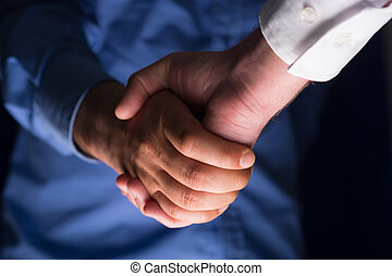 Handshake Handshaking in dark with low light - Two...