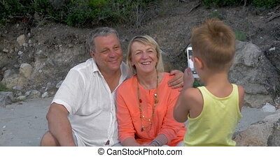 Child taking picture of grandparents with cell phone -...