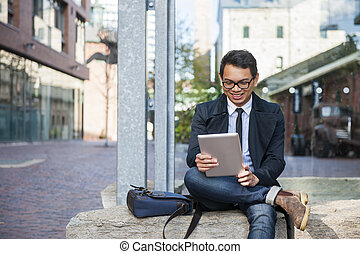 Young asian man looking at digital tablet - Young smiling...