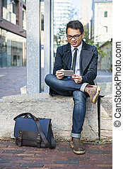 Young asian man looking at mobile phone - Young smiling...