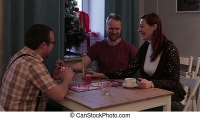 Family play a board game in a cafe - Caucasian people sit at...