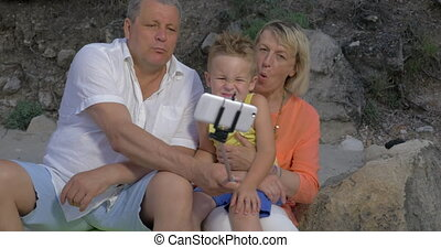 Grandparents and grandchild making funny mobile selfie -...