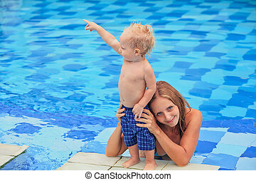 Little child swimming in pool with mother - Little happy...