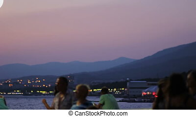 Sea Coast and Mountains after Sunset. People background