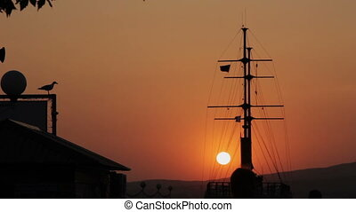 Silhouette of Ship in Dock At Sunset. Sun at orange sky