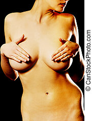Naked young woman covering her breast with hands