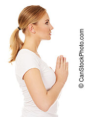Young woman praying - religion concept