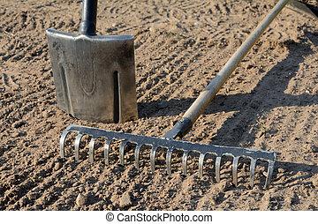 Rake and spade on soil - Rake and spade on loosened soil...