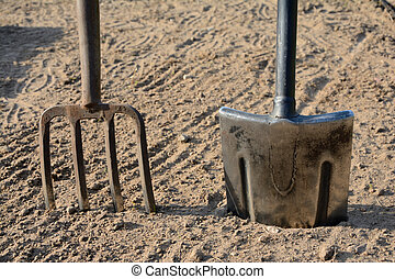 Pitchfork and spade stuck in the ground - Pitchfork and...