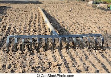 Rake on soil - Rake on loosened soil closeup