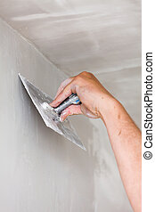 Home Renovation - Construction worker holding plastering...