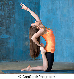 Beautiful woman doing one-legged Camel Pose - Beautiful...