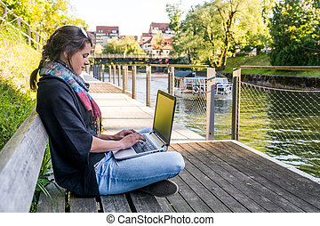 Young woman using laptop at a riverbank. Milleanial working...
