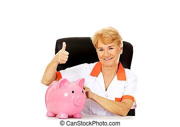 Smile elderly female doctor or nurse sitting behind the desk...
