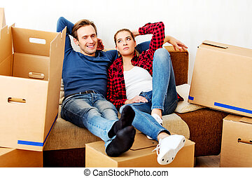 Happy tired couple sitting on couch in new home with...