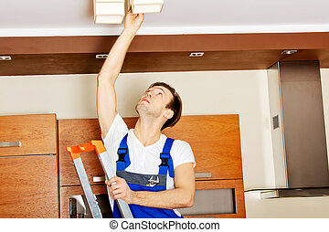 Young electrician working change a bulb at home.