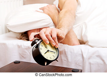 Man trying to sleep, when alarm clock ringing.