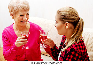 Happy senior woman with daughter or grandaughter drinking...