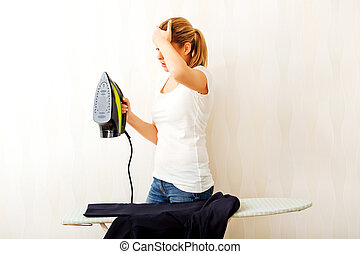 Young aghast woman standing behind ironing desk with iron in...