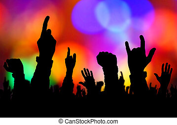 Silhouettes of concert crowd hands supporting band on stage...