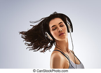 enjoys the music - beautiful young woman listening music in...