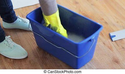 woman washing and squeezing rag in bucket at home - people,...