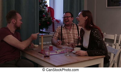 Three persons play a board game in a cafe - Caucasian people...