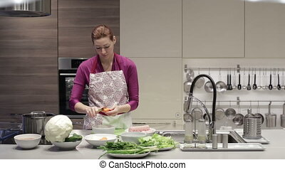 The woman in kitchen with a knife to clean carrots