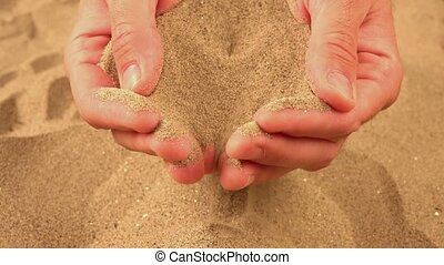 Handful of sand pouring through fingers, sand dust flowing...