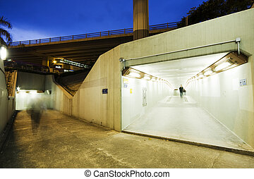 long tunnel with lamps and some people walking
