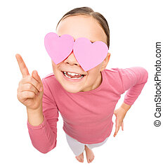 Little girl is holding hearts over her eyes, fisheye...