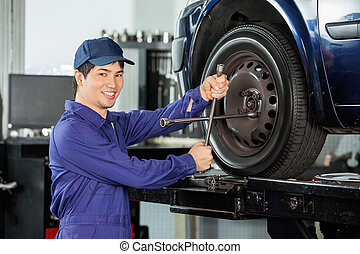 Confident Mechanic Fixing Car Tire - Portrait of confident...