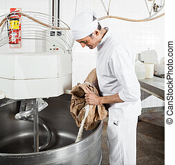 Mature Baker Pouring Flour In Mixing Machine - Mature male...