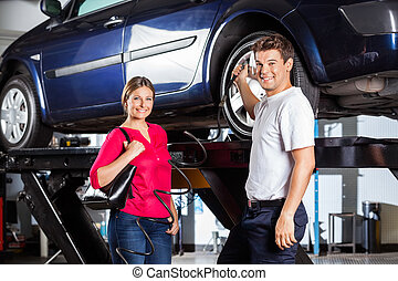 Customer Standing With Mechanic Filling Air In Tire -...