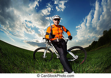Cyclist with the Bike on meadow - Cyclist on the Beautiful...