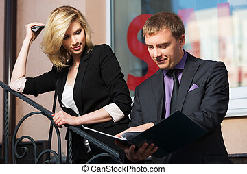 Young business couple with a folder against office building