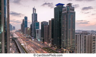 Downtown Dubai towers day to night timelapse. Aerial view of Sheikh Zayed road with skyscrapers after sunset.