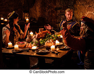 Medieval people eat and drink in ancient castle kitchen...