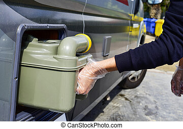 removing the sewage tank of a campervan - closeup of a young...