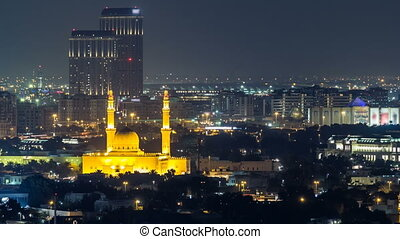 Dubai skyline with The Jumeirah Mosque illuminated at night...