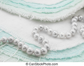 White pearl necklace closeup on turquoise and white frayed...