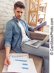 Young man working at home - Attractive young man is working,...