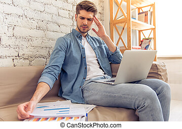 Young man working at home - Attractive tired young man is...