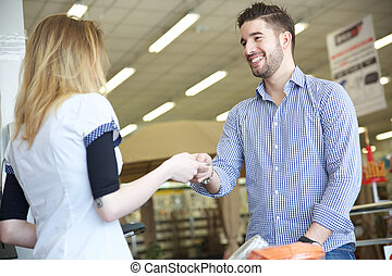 assistant cashier accepting credit card as payment for...