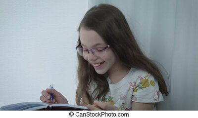Emotional little girl in glasses laughing at window -...