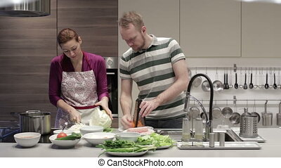 Young couple in the kitchen preparing dinner