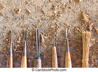 Old and well used wood carving chisels, on a old workbench