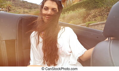 young woman at the backseat of a cabrio. summer feeling