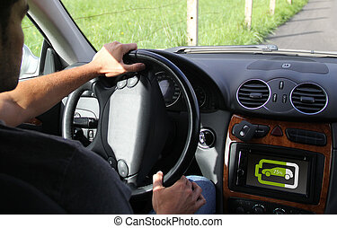 young man driving with battery information on digital...